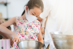 Asian child girl in cooking workshop for kid, holding kitchen equipment, wearing protective medical mask, child girl wearing floral pattern dress, space for text.