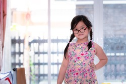 Asian child girl of Thai-Chinese descent stands sweet smile for photographer. She wears glasses for children with visual problem. Wear a pink floral skirt. Knit braids on both sides. Stay in the house