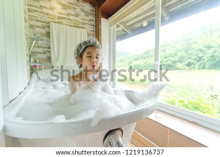 Asian Child girl taking bath in a bath tub washing hair with shampoo and soap. Kid playing with foam and water splashes in bathroom with nature view outside window.
