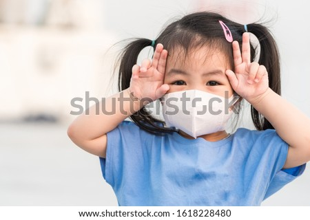 Asian child girl wearing a protection mask against PM 2.5 air pollution 2020 in Bangkok city. Thailand.