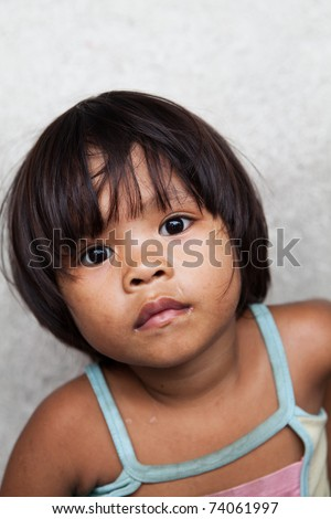 Asian child living in poverty - young Filipino girl against wall