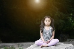 Asian child meditate zen or kid girl close eye mind meditating with breath and sit on rock or stone for peace or yoga relax with hand overlap in tree garden at outdoor temple park and warm golden sun