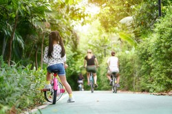 Asian child or back of kid girl and biker to cycling fun on bike with many people riding bicycles on public park or garden and green tree with road of bicycle for sport exercise to healthy on holiday
