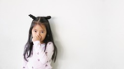 Asian child or kid girl hand covered or close nose to smelly or sneezing and cold sick to weak from virus bacteria or dust and allergy by weather on preschool for medical background and white space