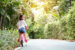 Asian child or kid girl smile and biker to cycling fun on bike or people riding bicycles on public park or garden and green tree with road of bicycle for sport exercise to healthy on family holiday