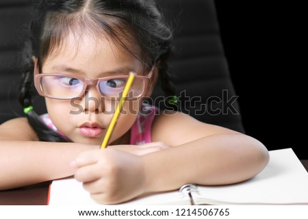 asian child or kid girl strabismus or squint-eyed make lasik with enjoy doing homework or learn write on white paper book and wear eyeglasses for short sighted on desk and black included clipping path