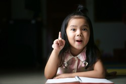 Asian child or kid girl student sleep reading and thinking for new idea with wow open mouth on homework and diary or book at children kindergarten classroom or nursery preschool in home on black space