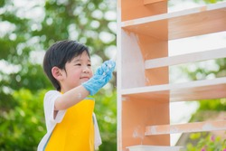 Asian child painting wooden shelf outdoors