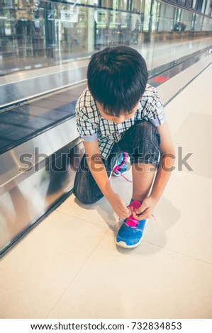 Asian child sitting and tying to tie shoelaces near electric speedwalk in modern airport. Do it yourself concept. Travel on vacation. Vintage film filter effect. #732834853