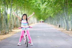 Asian child smile or kid girl wear face mask under chin and cycling fun on bike or people bicycle on public park with green garden and bamboo tree for sport exercise to healthy show fist and hand up