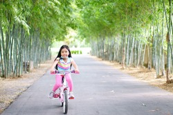 Asian child smile or kid girl wear face mask under chin and cycling fun on bike or people bicycle on public park with green garden and bamboo tree for sport exercise to healthy on summer relax holiday