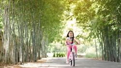 Asian child smile or kid girl wear face mask under chin and cycling fun on bike or people riding bicycle on public park and green garden or bamboo tree for sport exercise to healthy on summer holiday
