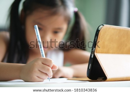asian child student back to school or kid girl smile write note or draw by pencil and read on computer tablet with doing homework to new idea think or people learn from home study online on smartphone ストックフォト ©