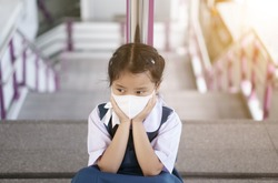 Asian child student or kid girl wearing white face mask for protect PM 2.5 dust or COVID-19 virus and sit against railing on sky train station or overpass stairway to bored sadly for back to school