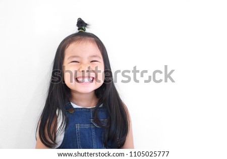 Asian children cute or kid girl and kindergarten student happy smile white teeth and laugh with wear dungarees jean for fashion or child dental on white background with space isolated stock photo
