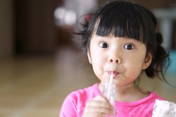 Asian children cute or kid girl drinking water or soy milk beverage in bottle by tube or straw and eating snack or dessert