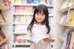Asian children cute or kid girl reading and choose tale or story book on bookshelf in library or bookstore at school for learning and studying