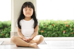 Asian children cute or kid girl sit for meditation with peace and relax in garden pavilion at temple or church and wearing white dress with sunlight on white with space