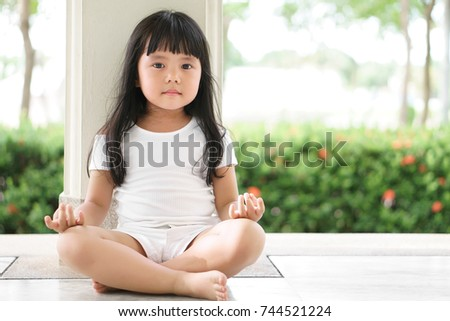 Asian children cute or kid girl sit for open eye meditation or yoga and for peace and relax or recreation in garden pavilion at temple or church and wearing white dress with nature sunlight and space