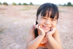Asian children cute or kid girl smile with laugh and happy fun because come back home to country and wear traditional top or sleeveless shirt sit on arid soil for agriculture at home