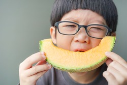 Asian Children eating a slice of a sweet delicious Japanese melon. Hungry kid biting from a piece of melon, Fruit and Dessert background concept