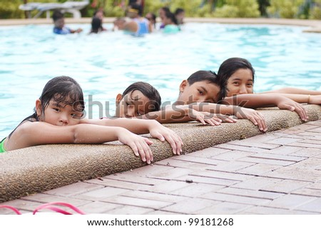 Asian children lining up at the pool side.
