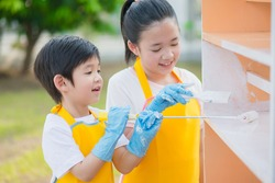 Asian children painting wooden shelf outdoors