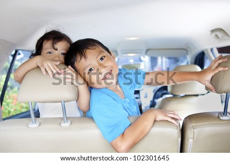 Asian children ready for a road trip posing in car