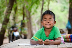 Asian children study at old home. Poor kid learning to drawing, painting with color pencil. Poverty child, smile, lying on dirty wooden table and writing on book. Poor Quality Education Concept.