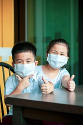 asian children wearing protection mask happiness at home while covid-19 virus infected in bangkok thailand
