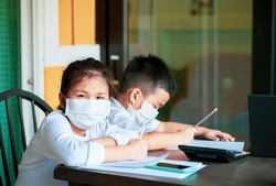 asian children wearing protection mask study at home school