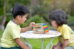 Asian children with popsicle sticks house in the outdoor.Young males with creative wooden innovation.Kids doing colorful model design craft.Homeschooling boy handmade activity project.