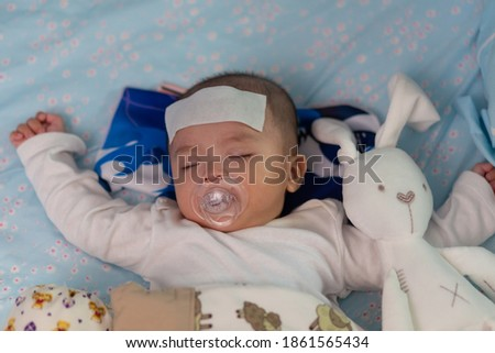 Asian Chinese baby sleeping during high fever with cool fever jel pad on forehead Zdjęcia stock ©