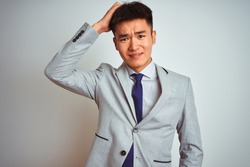 Asian chinese businessman wearing grey jacket and tie standing over isolated white background confuse and wonder about question. Uncertain with doubt, thinking with hand on head. Pensive concept.
