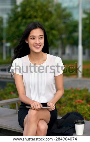 asian chinese businesswoman office worker communicating with tablet computer on coffee break outdoors
