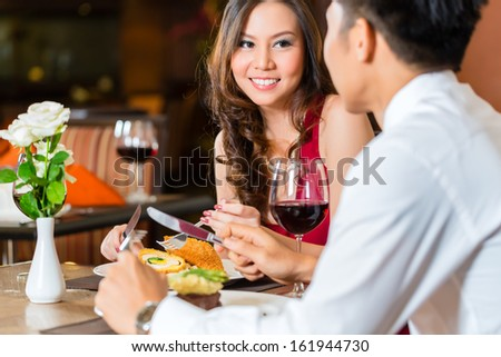 Asian Chinese Couple - Man And Woman - Or Lovers Flirting And Having A Date Or Romantic Dinner In A Fancy Restaurant