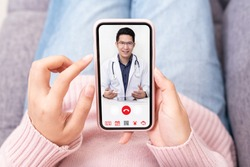 Asian chinese doctor or therapist help releave stress from coronavirus crisis video conference call online live talk remotely with woman sit on sofa couch at home using smartphone doctor consultation.