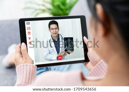 Asian chinese doctor video conference call online live talk follow up remotely in medical coronavirus result with asia woman sit at sofa couch at home. Online healthcare digital tech service concept.
