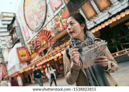 asian chinese female tourist in urban osaka japan. pretty woman traveler with paper map walking on street in tsutenkaku. elegant young girl holding travel guide while self-guided trip in spring.