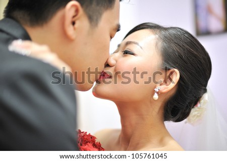Asian Chinese groom and bride kissing in their wedding day
