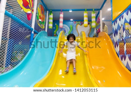 Asian Chinese little girl playing on the slide at indoor playground