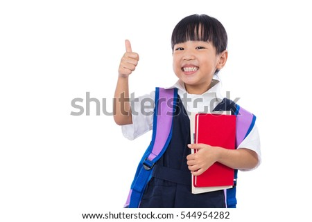 Asian Chinese little primary school girl with school uniform showing thumbs up in isolated white background.
