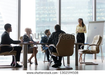 Asian coach presenter giving corporate business presentation at office board multi-ethnic team meeting, chinese manager speaking to diverse sales group training presenting new project on whiteboard