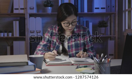 asian college female nerd stay up late at night studying preparing for math test. young girl counting on calculator to solve the problem on homework. concentrated lady in glasses shirt sitting home