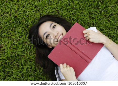 Asian College student lying on the grass on campus