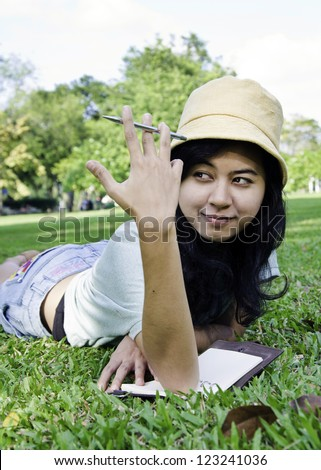 Asian college student studying outdoor in the park