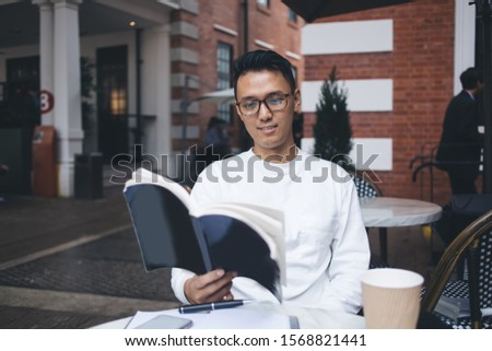 Asian concentrated cheerful guy reading interesting book with great concentration while preparing for college exams sitting alone in urban cafeteria