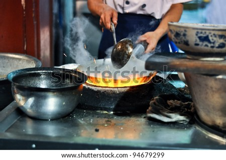 asian cook cooking with a wok on a gas flame