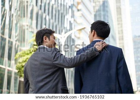 asian corporate executive giving subordinate a pat on the back while walking in street of central business district of modern city Stock photo ©
