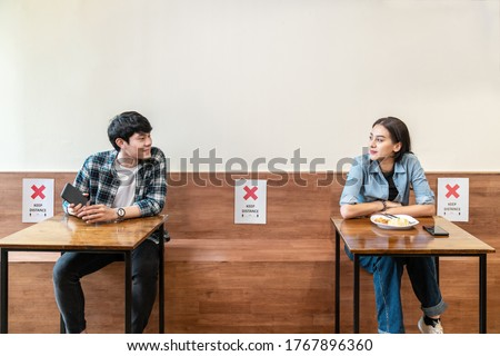 Asian couple at seat and keep distance, paper sign on seat at reopenning restaurant.